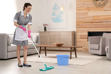 Photo for Chambermaid washing floor with mop in hotel room. Space for text - Royalty Free Image
