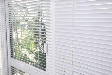 Photo pour Window with closed white horizontal blinds as background - image libre de droit