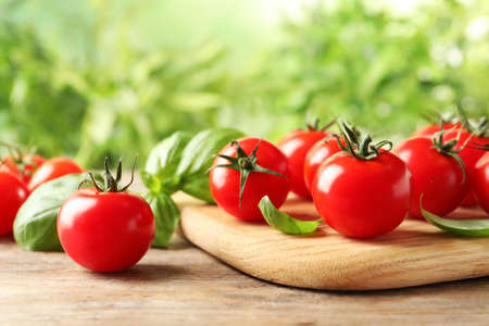 Photo for Board with fresh cherry tomatoes on wooden table - Royalty Free Image