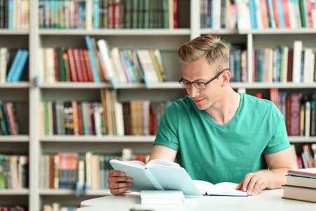 Foto de Young man reading book at table in library. Space for text - Imagen libre de derechos