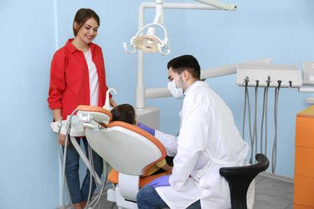Photo pour Professional dentist working with little patient in modern clinic - image libre de droit