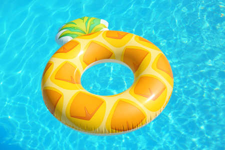 Photo for Bright inflatable pineapple ring floating in swimming pool on sunny day - Royalty Free Image