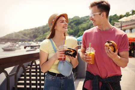 Foto de Young happy couple with burgers walking on city street - Imagen libre de derechos