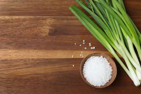Photo pour Fresh green onions and bowl of salt on wooden background, top view. Space for text - image libre de droit