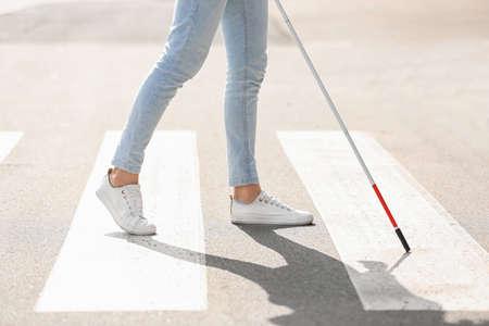 Photo pour Blind person with long cane crossing road, closeup - image libre de droit