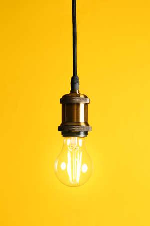 Photo pour Hanging modern lamp bulb against yellow background - image libre de droit