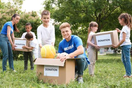 Photo pour Volunteers and kids with donation boxes in park - image libre de droit