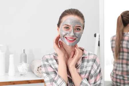 Young woman with cleansing mask on her face in bathroom. Skin care