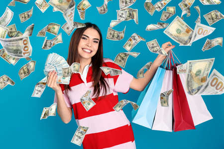 Photo for Happy young woman with dollars and shopping bags under money rain on blue background - Royalty Free Image