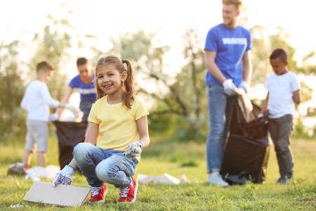 Foto de Little girl collecting trash in park. Volunteer project - Imagen libre de derechos