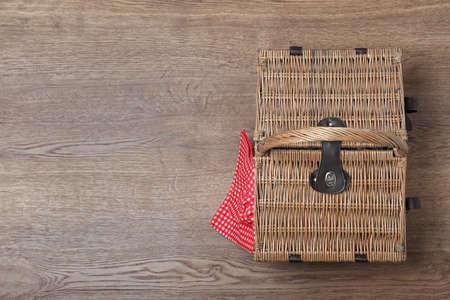 Photo pour Closed wicker picnic basket on wooden table, top view. Space for text - image libre de droit