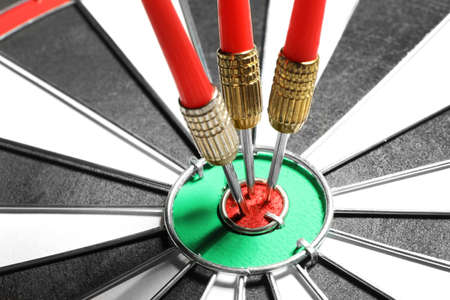 Foto de Dart board with red arrows hitting target, closeup - Imagen libre de derechos