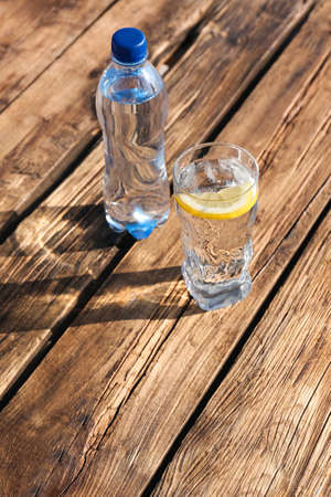 Photo for Glass and bottle of refreshing drink for hot summer day on wooden table, space for text - Royalty Free Image