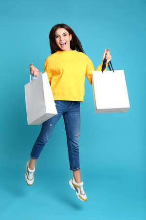 Photo pour Happy young woman with paper bags jumping on blue background - image libre de droit