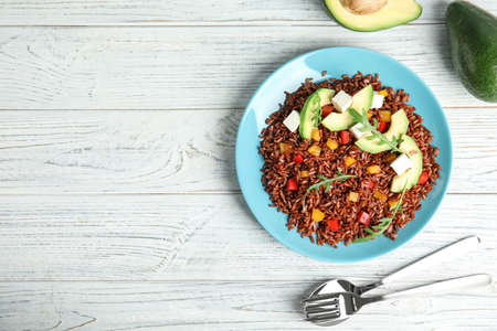 Foto de Flat lay composition with delicious cooked brown rice on white wooden table. Space for text - Imagen libre de derechos