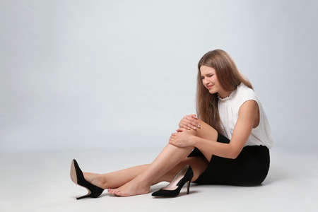 Photo pour Full length portrait of businesswoman with knee problems sitting on grey background - image libre de droit