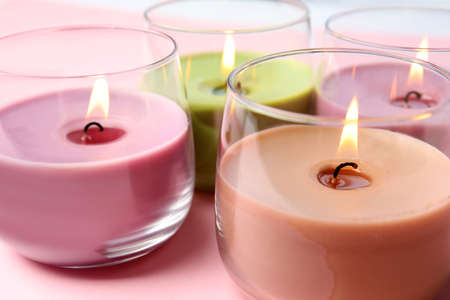 Photo for Burning wax candles in glass holders on pink background, closeup - Royalty Free Image