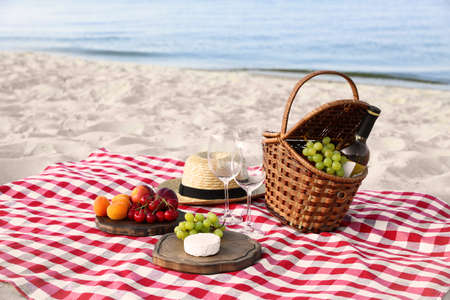 Photo pour Checkered blanket with picnic basket and products on sunny beach - image libre de droit