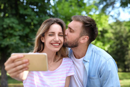 Photo for Happy young couple taking selfie in park - Royalty Free Image