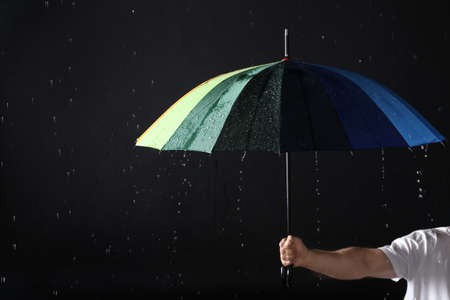 Photo for Man holding color umbrella under rain against black background, closeup - Royalty Free Image