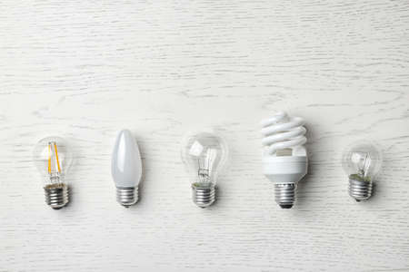 Photo for Set of different lamp bulbs on white wooden background, top view - Royalty Free Image