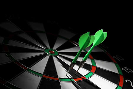 Foto de Green arrows hitting dart board against black background. Space for text - Imagen libre de derechos