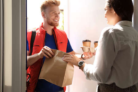 Photo pour Courier giving order to young woman at open door. Food delivery service - image libre de droit