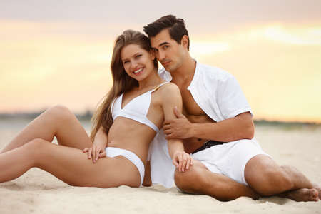 Photo pour Happy young couple relaxing together on sea beach at sunset - image libre de droit