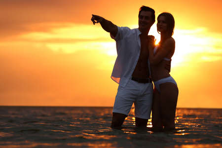 Photo pour Happy young couple spending time together on sea beach at sunset - image libre de droit