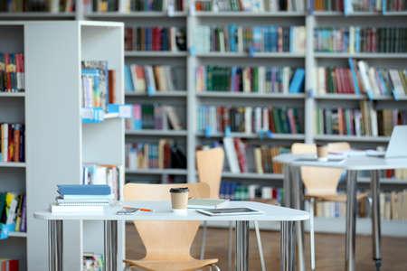 Foto de Tablet, drink and books on table in library - Imagen libre de derechos