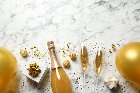 Flat lay composition with bottle of champagne for celebration on white marble background. Space for text