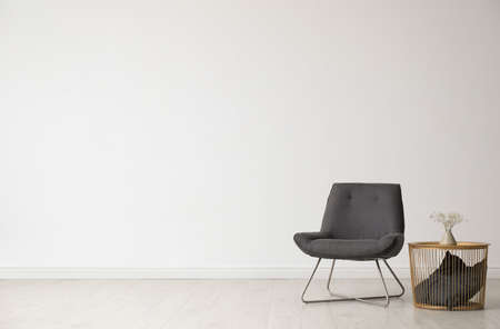 Photo pour Stylish living room interior with comfortable chair and side table near white wall. Space for text - image libre de droit