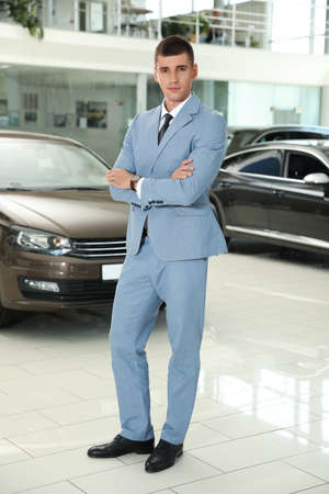 Photo pour Young salesman near new car in modern dealership - image libre de droit