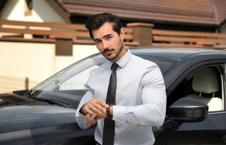 Photo pour Attractive young man checking time near luxury car outdoors - image libre de droit