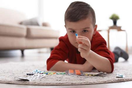 Foto de Little child with different pills on floor at home. Household danger - Imagen libre de derechos