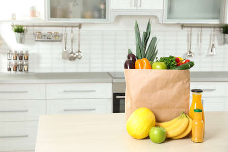 Photo pour Paper shopping bag full of vegetables with fruits and juice on table in kitchen. Space for text - image libre de droit