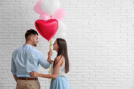 Photo pour Young couple with air balloons near white brick wall. Celebration of Saint Valentine's Day - image libre de droit