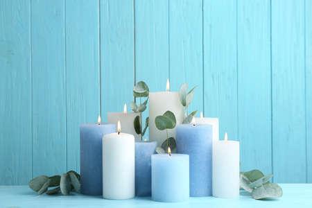 Photo pour Set of burning candles with eucalyptus on table against light blue wooden background - image libre de droit