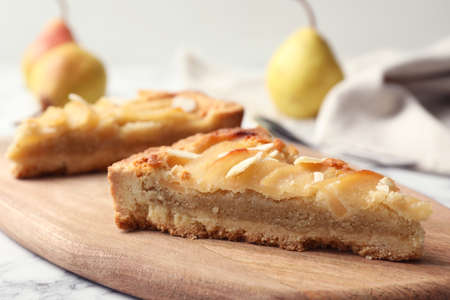 Photo pour Board with pieces of delicious sweet pear tart on table, closeup - image libre de droit