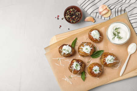 Delicious baked potato with sour cream served on light grey table, flat lay. Space for text