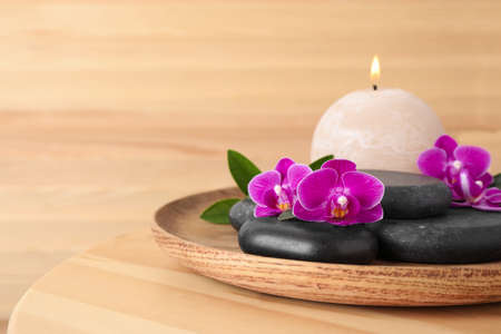 Foto de Tray with spa stones, orchid flowers and candle on wooden table. Space for text - Imagen libre de derechos