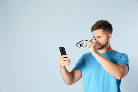 Photo pour Young man with vision problems using smartphone on grey background, space for text - image libre de droit