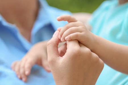 Photo pour Young mother holding her child's hand, closeup - image libre de droit