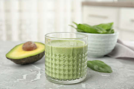Photo for Glass of tasty avocado smoothie on light grey marble table - Royalty Free Image
