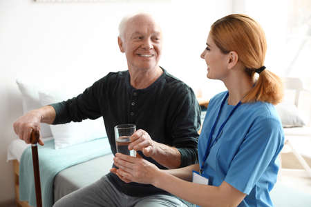 Photo for Nurse giving glass of water to elderly man indoors. Medical assistance - Royalty Free Image