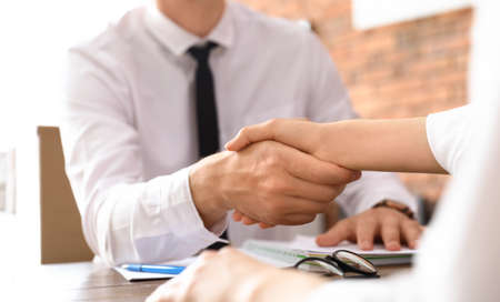 Photo pour Business partners shaking hands at table after meeting in office, closeup - image libre de droit