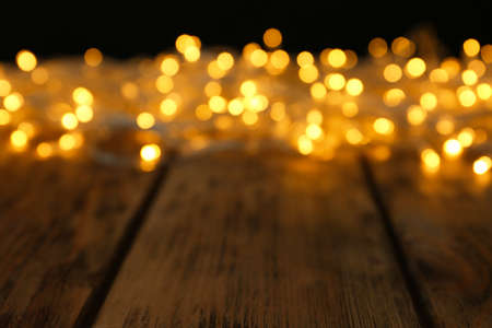 Photo pour Blurred view of glowing Christmas lights on wooden table - image libre de droit