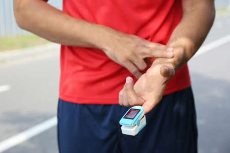 Young man checking pulse with medical device after training, closeup