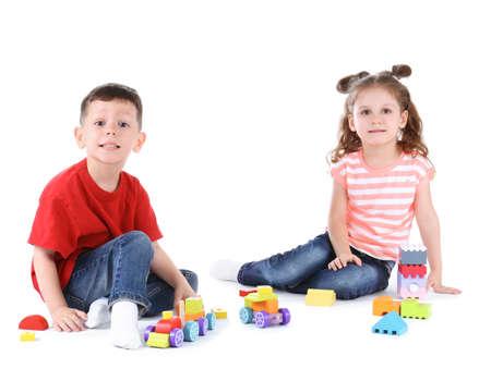 Foto de Cute little children playing with toys on white background - Imagen libre de derechos