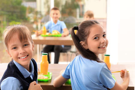 Happy girls at table with healthy food in school canteen